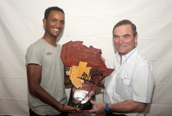 Natnael Berhane recevant le trophée de meilleur coureur d'Afrique par Bernard Hinault